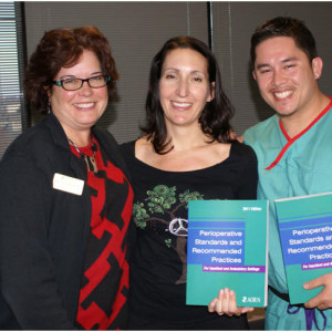 Bonnie Denholm, MS, BSN, RN, CNOR, presents two student winners with AORN textbooks she personally helped produce.